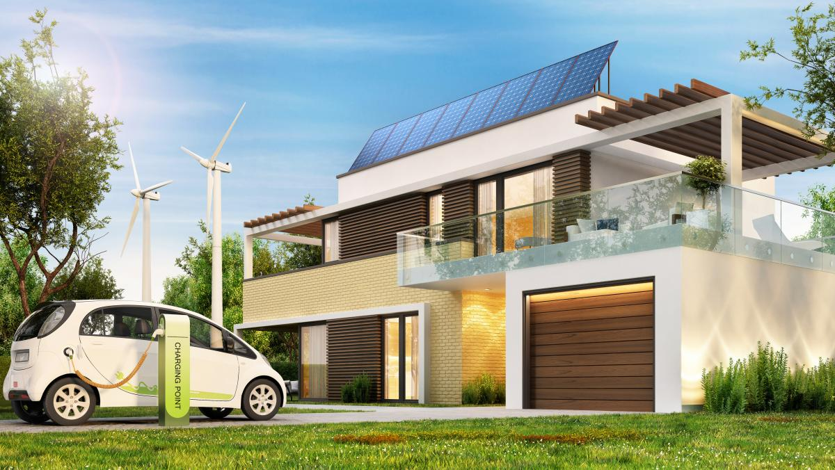 Modern eco house with solar panels and wind turbines and an electric car.